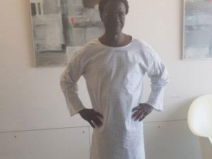 Ein farbiger Mann posiert mit weißem Nachthemd im Krankenzimmer